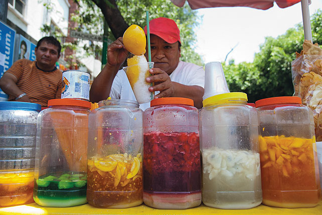 A woman stands outdoors behind a counter with several clear plastic containers containing fluids of different colors and with chopped up fruit in them. She holds a plastic cup with shaved ice, and using a ladle she pours an orange fluid from one of the containers over the ice. And man watches from the background.