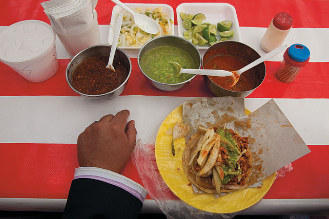 Table with taco and sauces. The hand of man wearing a suit rests on the table. There's a taco on a plastic plate. Napkins, toothpicks, salt shaker, limes. Red and white striped table cloth.