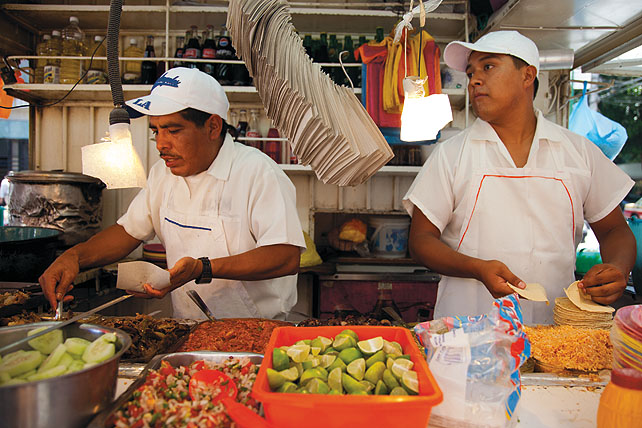 Two street food vendors preparing food and taking orders. In the front is an orange bin with limes cut in quarters, a metal bin with salsa. One of the chefs is handling tortillas, the other is scooping carne asada onto a paper napkin, probably with a tortilla inside. In the background there are shelves with bottles of cooking oil, and bottles of Coca-Cola. A huge stack of napkins are hanging from a hook in the foreground.