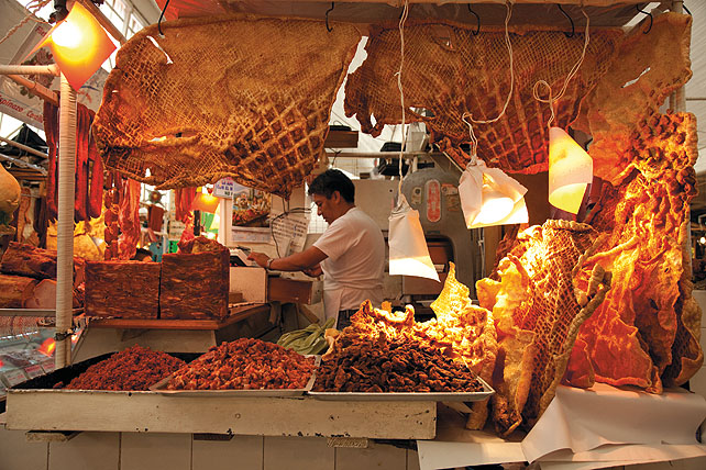 A meat vendor stands inside his stall in an indoor market hall. Huge slabs of chicharrón are hanging in the foreground and leaning towards a pole on the counter. A man is in the background working by the register.