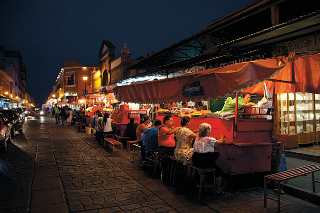 A night street scene from Mexico. A cobbled street lined with food vendors, and their customers' sitting down to eat.