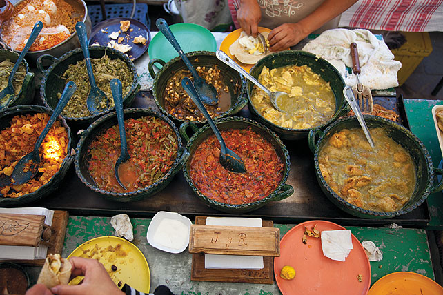 Several pots with colorful sauces and stews, each with a metal serving spoon. In the upper edge of the photo there is a pair of hands preparing a taco on a plastic plate. In the lower edge of the photo there is a pair of hands holding a taco, apparently ready to eat.