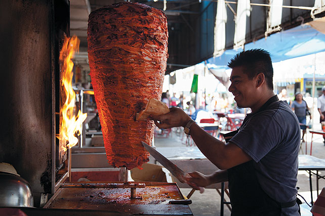 Tacos al pastor: A man standing in front of a vertical spit rotisserie, cutting meat from the spit onto a tortilla.