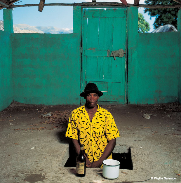 A man stands in a square hole in the dirt floor. The walls around him are green. He wears a yellow shirt with a black pattern, and a hat. In front of him is a bottle and a big, white metal cup.