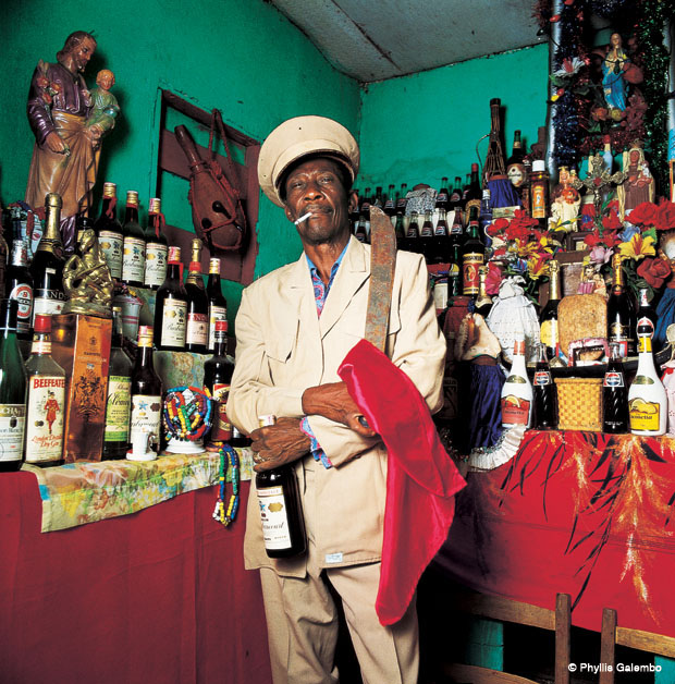 Photograph of man holding up a machete, a red handkerchief and a bottle. He stands in a room with green walls. Shelves full of different types of bottles, alcoholic and non-alcoholic beverages, line the walls. There are also some religious sculptures on the shelves.