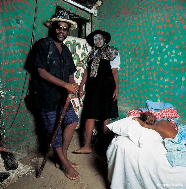 A man and a woman stands in a small room, leaning against the walls. The walls are painted green with red dots. The woman's face is painted light green. The man wears a hat and sunglasses. He holds a cane. On a bed is a child, sleeping.