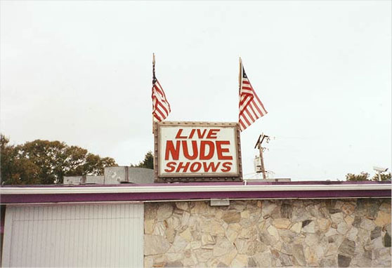"Photo of sign advertising ""live nude shows"""