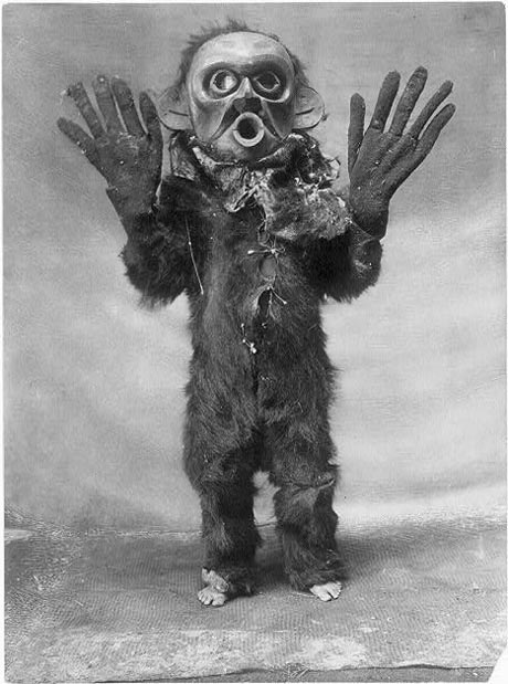 Black and white photo of native American with mask.