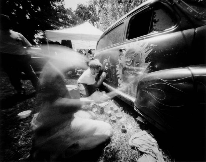 Black and white photo of two people painting figures reminiscent of Rat Fink onto a car at a car show.