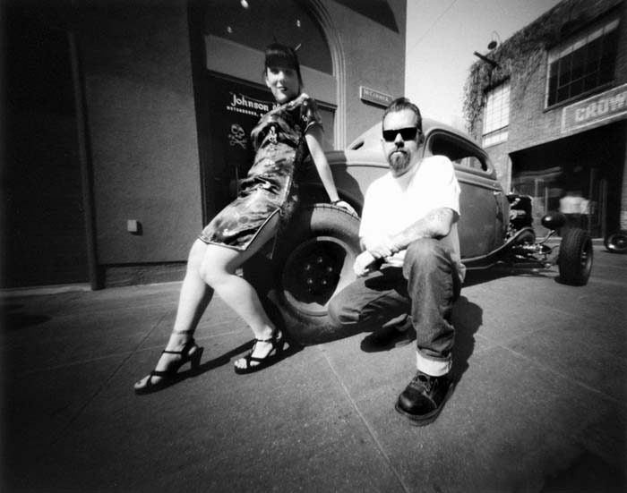 Black and white photo of a young man and woman standing in front of a hot rod in an alley next to the Pasadena Johnson Motor Sports store.