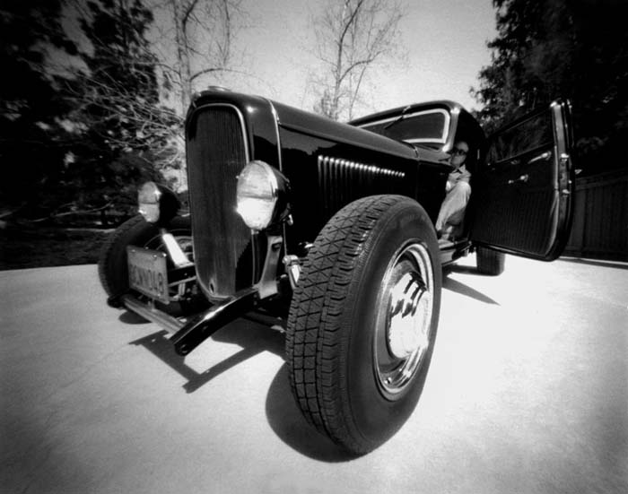 Black and white photo of painter Robert Williams seated inside his 1932 Ford hot rod.