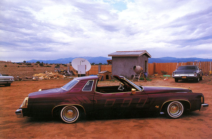 Lowrider from New Mexico: A 1977 Pontiac Grand Prix in a rural yard, mountains far in the background.