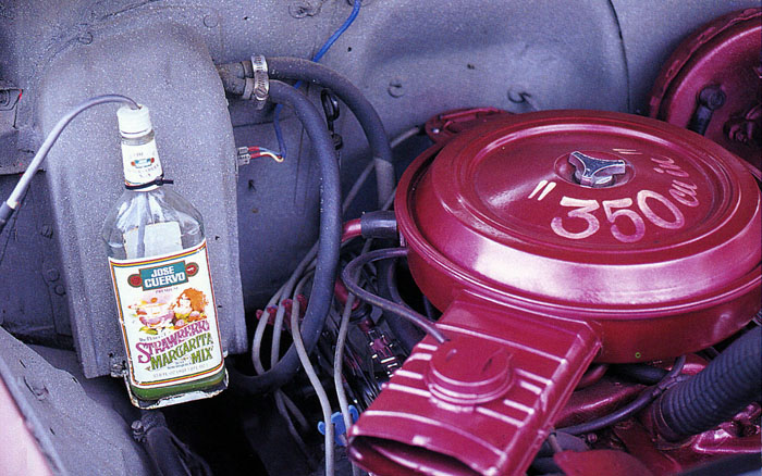 Engine room of 1950 Chevrolet, with Tequila bottle holding coolant fluid