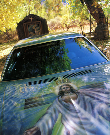 New Mexico lowrider parked in front of simple chapel among trees. Mural on hood of car shows Jesus Christ.