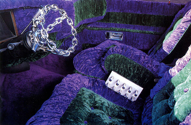 Interior of lowrider. Green and purple crushed velvet. Chrome plated chain steering wheel. Control panel for hydraulics.