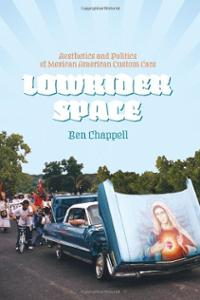 [Book cover of Lowrider Space shows a a baby-blue and white lowrider in a residential neighboorhood, on a paved street with no pavements. The car has the engine compartment open, and the lid is hinged in the front, so the artwork on the lid can be seen from the front of the car. It is an airbrushed painting of the Holy Mary with the Immaculate Heart. Behind the car follows a procession of kids on bicycles, dancers dressed in Aztec ritual attire, and a photographer. Two young men stands in front of a house, watching.]