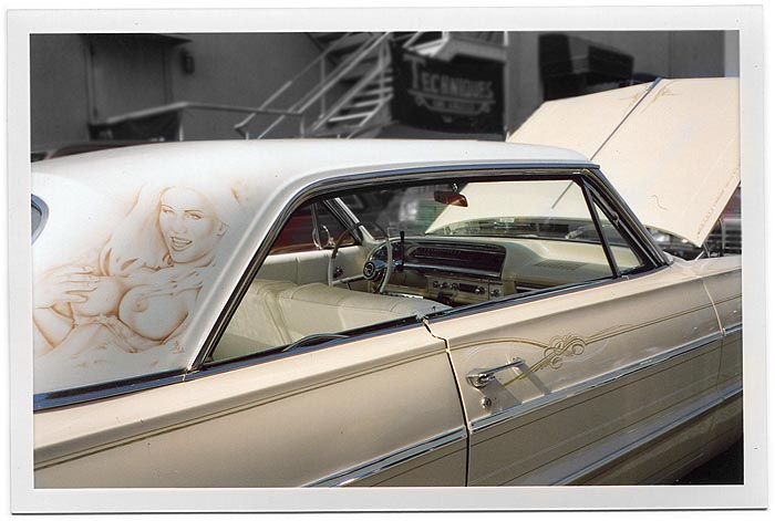 "Cream colored lowrider car photographed at angle from rear right. Brown, monochrome mural of topless woman fondling hear right breast with her right hand, smiling. Pinstripes on side of car. In background, behind car, banner with ""Techniques Los Angeles"""