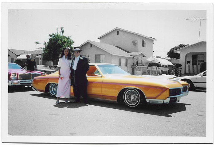 Lowrider car parked on residential street. In front of the car stands a teenage boy and a teenage girl, dressed up in a suit and a dress.