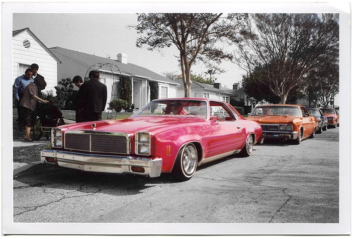 Lowrider cars parked on residential street.