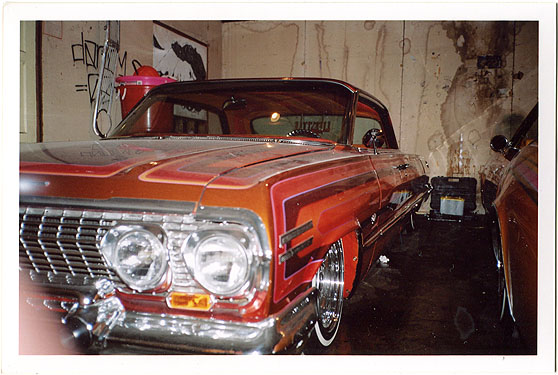 Lowrider car parked in garage. Water damage on the garage walls behind the car. Black and white poster showin Jim Morrison on garage wall, hung sideways. Some spraypainted black tag on the wall. Finger of photographer slightly covering camera lens.